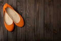 Orange Frauen ` s beschuht Ballerinen auf hölzernem Hintergrund Stockfotos