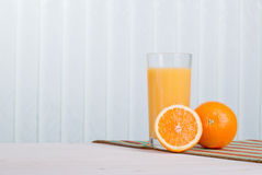 Orange fresh juice beside delicious ripe oranges on the table Royalty Free Stock Photos