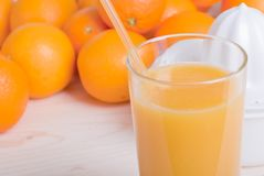 Orange fresh juice beside delicious ripe oranges on the table Stock Photography