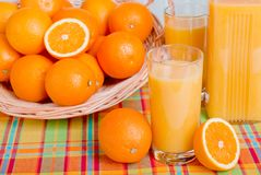 Orange fresh juice beside delicious ripe oranges on the table Royalty Free Stock Photography