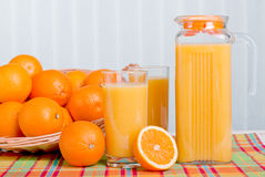 Orange fresh juice beside delicious ripe oranges on the table Royalty Free Stock Photo