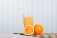 Orange fresh juice beside delicious ripe oranges on the table. Orange fresh juice beside delicious ripe oranges the table Stock Photo