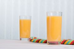 Orange fresh juice beside delicious ripe oranges on the table Royalty Free Stock Images