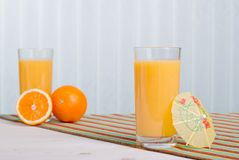 Orange fresh juice beside delicious ripe oranges on the table. Orange fresh juice beside delicious ripe oranges the table Stock Photography