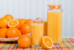 Orange fresh juice beside delicious ripe oranges on the table. Orange fresh juice beside delicious ripe oranges the table Royalty Free Stock Image
