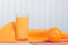 Orange fresh juice beside delicious ripe oranges on the table. Orange fresh juice beside delicious ripe oranges the table Stock Photos