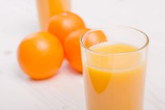 Orange fresh juice beside delicious ripe oranges on the table. Orange fresh juice beside delicious ripe oranges the table Royalty Free Stock Photos