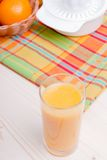 Orange fresh juice beside delicious ripe oranges on the table. Orange fresh juice beside delicious ripe oranges the table Royalty Free Stock Photo