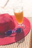 Orange fresh juice, hat and sunglasses over sea Stock Images