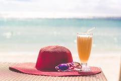 Orange fresh juice, hat and sunglasses over sea Stock Photography