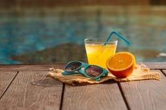 Orange fresh juice smoothie drink, sunglasses near swimming pool.  stock images
