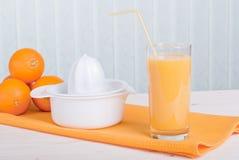 Orange frischer Saft neben köstlichen reifen Orangen auf dem Tisch Lizenzfreies Stockfoto