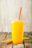 Orange Frozen Slushie in Plastic Cup with Straw Royalty Free Stock Image