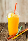 Orange Frozen Slushie in Plastic Cup with Straw Stock Image