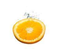 Orange Frucht, die im Wasser spritzt lizenzfreie stockbilder