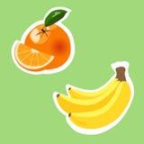 Orange Frucht und Bananen auf grünem Hintergrund Stockfoto