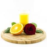 Orange - Frucht und Saft auf hölzernem Brett mit rosafarbener Blume Lizenzfreies Stockfoto