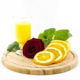 Orange - Frucht und Saft auf hölzernem Brett mit rosafarbener Blume Stockfotos