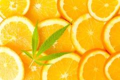 Orange Fruchtscheiben und Marihuanablatt stockbilder