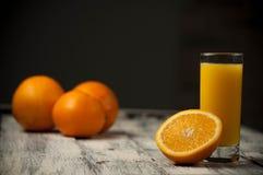 Orange Fruchtschnitt und Orangensaft auf Holztischhintergrund, Stockfoto
