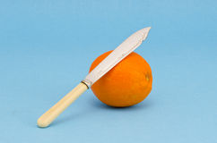 Orange fruit with antique knife Stock Image
