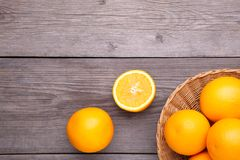 Orange fruit in basket on a grey background royalty free stock photos