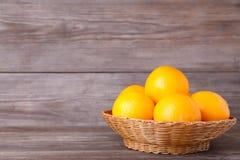 Orange fruit in basket on a grey background royalty free stock photography