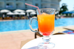 Orange fruit cocktail near pool on the table Stock Images