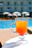 Orange fruit cocktail near pool on the table Royalty Free Stock Photography