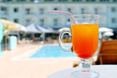 Orange fruit cocktail near pool on the table Stock Image
