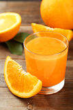 Orange fruit and glass of juice on brown wooden background Stock Photo