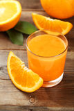 Orange fruit and glass of juice on brown wooden background. Royalty Free Stock Image