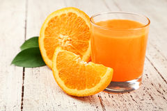 Orange fruit and glass of juice on white wooden background Royalty Free Stock Photos