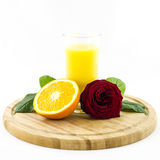 Orange - fruit and juice on wooden board with rose flower. Composition of orange fruit and juice on wooden board with rose flower royalty free stock photo