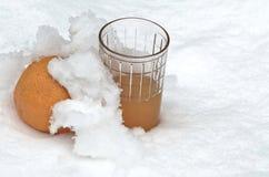 Orange fruit and orange juice refrigerate in the snow-drift at garden Stock Photo