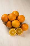 Orange fruit. Oranges in a basket over a wooden surface seen from above royalty free stock images