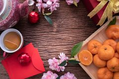 Orange fruit, pink cherry blossom and Chinese new year composition set on wood table, Chinese new year celebration background royalty free stock photography