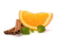 Orange fruit segment, cinnamon sticks and mint. Hot drinks ingredients. Orange fruit segment, cinnamon sticks and mint isolated on white background. Hot drinks stock image