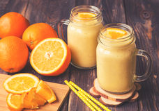 Orange fruit smoothie in the glass jars. With fresh orange slices on rustic wooden background. Vintage toned picture Royalty Free Stock Photo