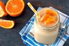 Orange fruit smoothie in a mason jar over slate background Stock Photography