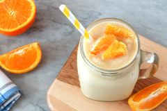 Orange fruit smoothie in a mason jar with straw Stock Photos