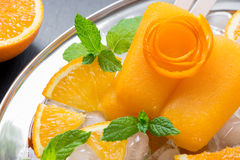 Orange fruit sorbet ice cream popsicles. Orange sorbet ice cream decorated with a flower of orange peel, mint leaves on silver plate with ice cubes, orange Stock Photography