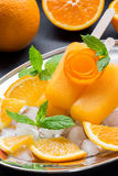 Orange fruit sorbet ice cream popsicles. Orange sorbet ice cream decorated with a flower of orange peel on silver plate with ice cubes, orange pieces, mint near Royalty Free Stock Photography
