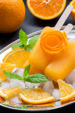 Orange fruit sorbet ice cream popsicles. Orange sorbet ice cream decorated with a flower of orange peel on silver plate with ice cubes, orange pieces, mint near Royalty Free Stock Photo