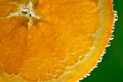 Orange fruit in sparkling water. Highlighted orange fruit in sparkling water Royalty Free Stock Photo