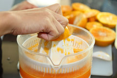 Orange fruit squeezed with woman hand in juicer machine Royalty Free Stock Photography