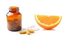 Orange fruit with vitamin c tablet on white background Stock Photos