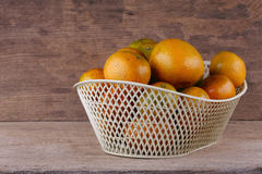 Orange fruit in white basket on wood table Royalty Free Stock Images