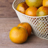 Orange fruit in white basket on wood table Stock Photography