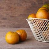 Orange fruit in white basket on wood table Stock Photography